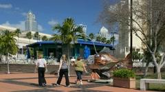 People walking Tampa riverwalk toward Convention Center Stock Footage