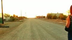 Young Woman Walks In Small Desert Town Stock Footage