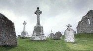 Stock Video Footage of Christian Celtic Cross grave Crosses in Graveyard in Ireland pan to old Church