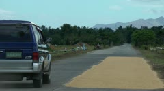 Drying harvested rice along a road  Philippines Stock Footage
