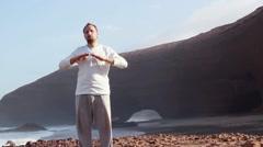 Man doing breathing exercises on Legzira beach HD Stock Footage