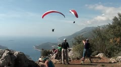 Parachutes paragliding overhead of tourists Stock Footage