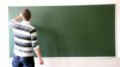 Boy writing on the blackboard Stock Footage