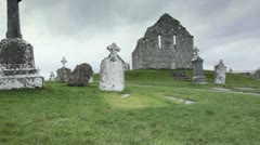 Christian Celtic Cross Crosses in Graveyard pan from old Church Stock Footage