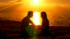 Young Couple Talking By Golden Shining Sea Wide Shot Stock Footage
