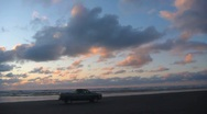 Stock Video Footage of Pickup Truck Driving on Ocean Beach at Sunset