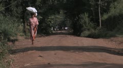 African woman carries supplies on her head - stock footage