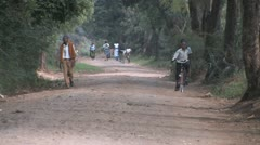 Boy rides bicycle along African road Stock Footage
