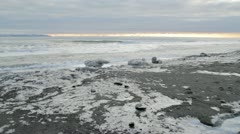 Waves rolling in on an icy Alaskan beach at sunset. Stock Footage