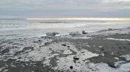 Stock Video Footage of Waves rolling in on an icy Alaskan beach at sunset.