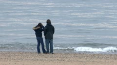 Young teenage couple whale watching from beach Stock Footage