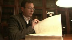 The man flips through an old book Stock Footage