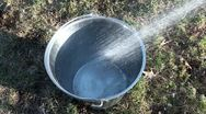 Pouring water into metal bucket Stock Footage
