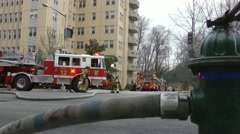 Fire fighters hustle at fire; fire hydrant Stock Footage