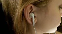 Ear with the earpiece (the Girl listens to music) - stock footage