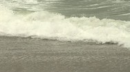 Waves crash on to sandy beach Stock Footage