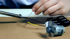 Young creator soldering together electronics - stock footage