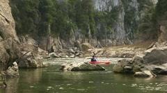Young man on red kayak paddling for fun among rocks Stock Footage