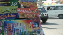 Pakistan traffic behind a magazine shop on the roadside - stock footage
