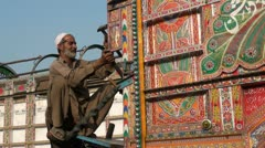 A man is fixing part of a truck in Pakistan - stock footage