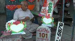 Man painting number plates in Pakistan Stock Footage
