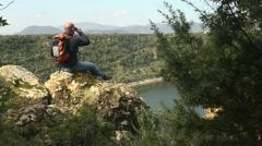 Adult man with binoculars sitting on rock, looking at lake - stock footage