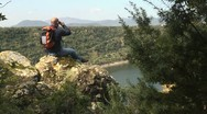 Adult man with binoculars sitting on rock, looking at lake Stock Footage