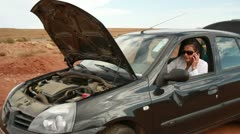 Upset businesswoman  with cellphone in the broken car, outdoors Stock Footage