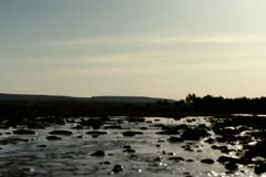 Silhouette of woman running across stream, slow motion Stock Footage