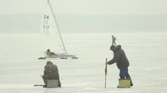 Fishermen on lake ice in winter, ice sailer passing by - stock footage