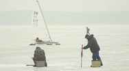 Fishermen on lake ice in winter, ice sailer passing by Stock Footage
