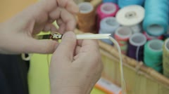 Stock Footage - Older Woman working with thread to make crafts Stock Footage