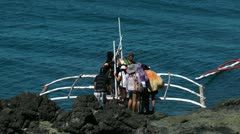 Loading on people on to traditional Filipino outriggers in the Philippines Stock Footage