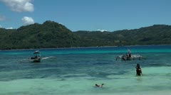 People relaxing in the clear water at Nogas island in the Philippines Stock Footage