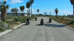4 Motorcycles From Behind Cruising In Small Desert Town Stock Footage