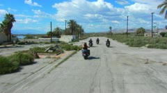 4 Motorcycles Away From Camera On Old Desert Road 1 Stock Footage