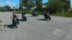 4 Motorcycles Around Curve And To Camera In Small Desert Town Stock Footage