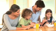 Family in the kitchen with bowls of cereal Stock Footage