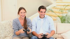 Man and woman sitting on the couch playing console games Stock Footage