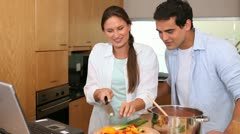Couple cooking while reading the recipe on a laptop - stock footage