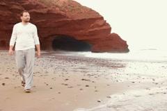 Man walking on beautiful Legzira beach NTSC Stock Footage