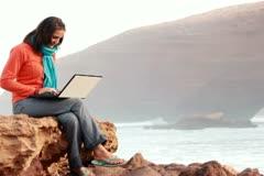 Woman with laptop sitting on the rocks, Legzira beach NTSC Stock Footage