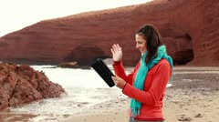 Young woman chatting on tablet computer on beautiful Legzira beach HD Stock Footage