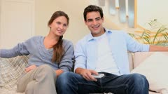 Couple laughing while watching televison Stock Footage