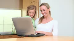 Woman choosing a recipe with her daughter - stock footage
