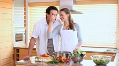 Husband tasting his wife's cooking with a spoon - stock footage