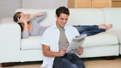 Nainen musiikin kuuntelu kun hänen miehensä lukee sanomalehteä Arkistovideo