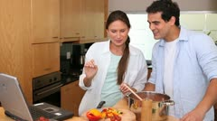 Laughing couple looking a recipe on a laptop - stock footage