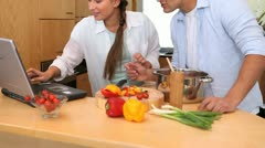 Couple reading a recipe on a laptop - stock footage