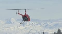 Chopper Hovering Backwards by Snowy Mountains Stock Footage